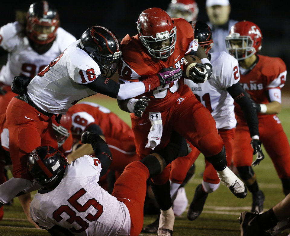 Photo - Carl Albert's Chantz Woodberry carries up the middle and is met by Del City's Khalil Warren (18) in high school football action as the Carl Albert Titans play the Del City Eagles on Friday, Nov. 15, 2013 in Midwest City, Okla. Photo by Steve Sisney, The Oklahoman