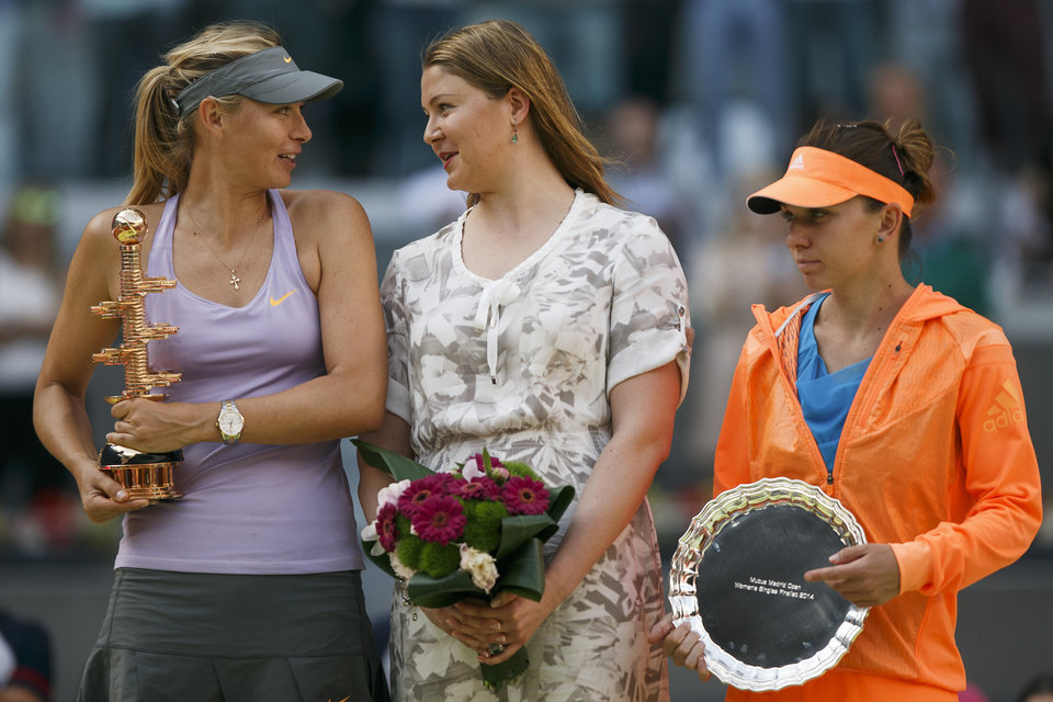 Photo - Maria Sharapova from Russia, left, celebrates her victory holding her trophy as she talks to former tennis player Dinara Safina, center, and Simona Halep from Romania, right, after a Madrid Open tennis tournament final match in Madrid, Spain, Sunday, May 11, 2014. (AP Photo/Andres Kudacki)