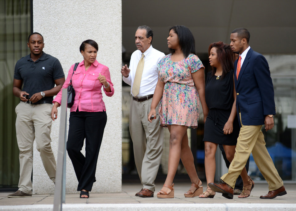 Photo - Family members of former New Orleans Mayor Ray Nagin, including his father Clarence Ray Nagin, Sr., center, leave federal court after the former mayor's sentencing in New Orleans, Wednesday, July 9, 2014. Nagin was sentenced Wednesday to 10 years in prison for bribery, money laundering and other corruption that spanned his two terms as mayor, including the chaotic years after Hurricane Katrina hit in 2005. (AP Photo/Andrea Mabry)