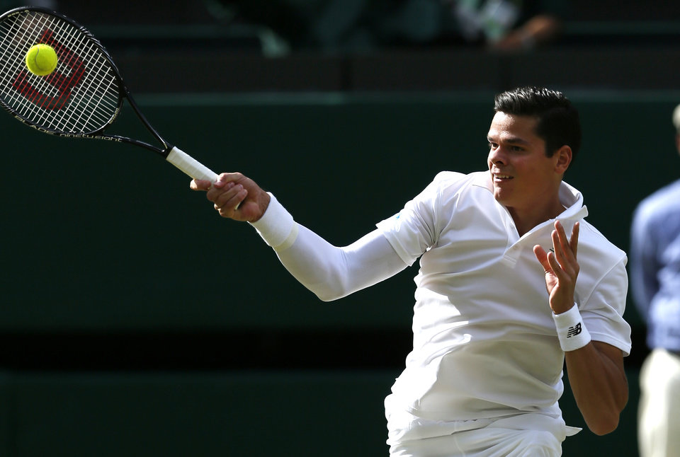 Photo - Milos Raonic of Canada plays a return to  Roger Federer of Switzerland during their men's singles semifinal match at the All England Lawn Tennis Championships in Wimbledon, London, Friday, July 4, 2014. (AP Photo/Ben Curtis)