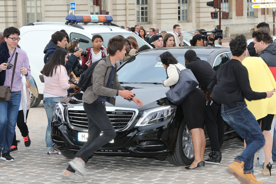 Photo - Fans gather to watch guests arriving, as they look inside one of the cars for Kim Kardashian, Kanye West and their guests, at the entrance  of the Chateau de Versailles  in Versailles, France, west of Paris, Friday, May 23, 2014.  The gates of the Chateau de Versailles, once the digs of Louis XIV, will be thrown open to Kim Kardashian, Kanye West and their guests for a private evening on the eve of their marriage. (AP Photo/Jacques Brinon)