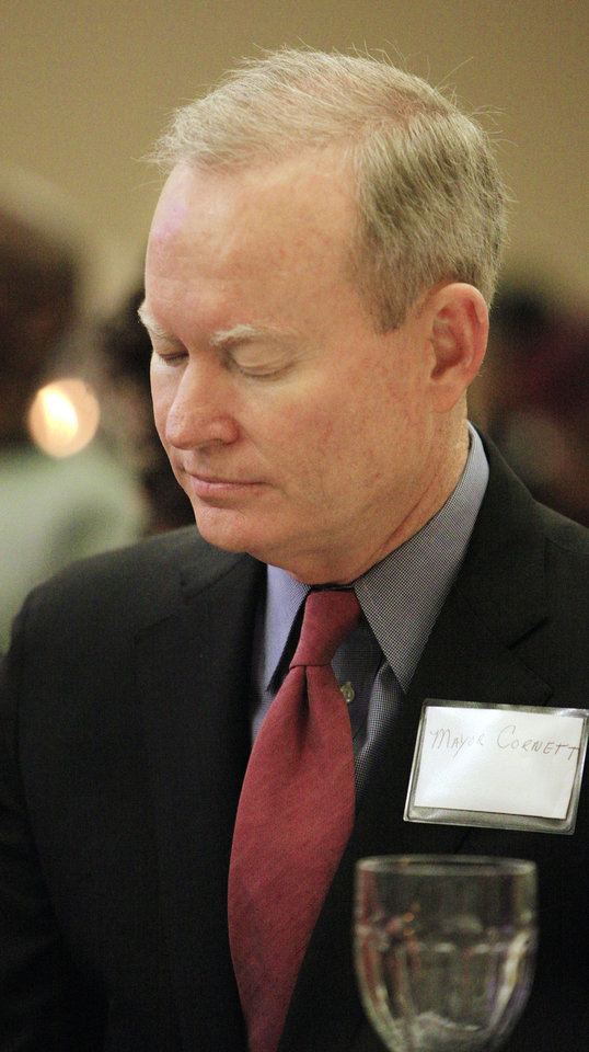 Photo - Oklahoma City Mayor Mick Cornett bows his head in prayer during the 17th annual Midwest City Dr. Martin Luther King Jr. Prayer Breakfast on Monday in MIdwest City.   PAUL B. SOUTHERLAND - PAUL B. SOUTHERLAND