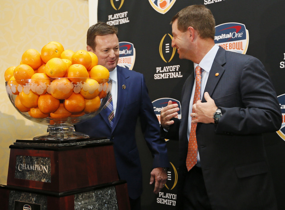 Photo - OU coach Bob Stoops, left, and Clemson coach Dabo Swinney talk before posing for photos during a news conference for the Capital One Orange Bowl, a College Football Playoff Semifinal game, at the Renaissance Fort Lauderdale Cruise Port Hotel in Fort Lauderdale, Florida, Wednesday, Dec. 30, 2015. The Oklahoma Sooners will play the Clemson Tigers on News Year's Eve. Photo by Nate Billings, The Oklahoman