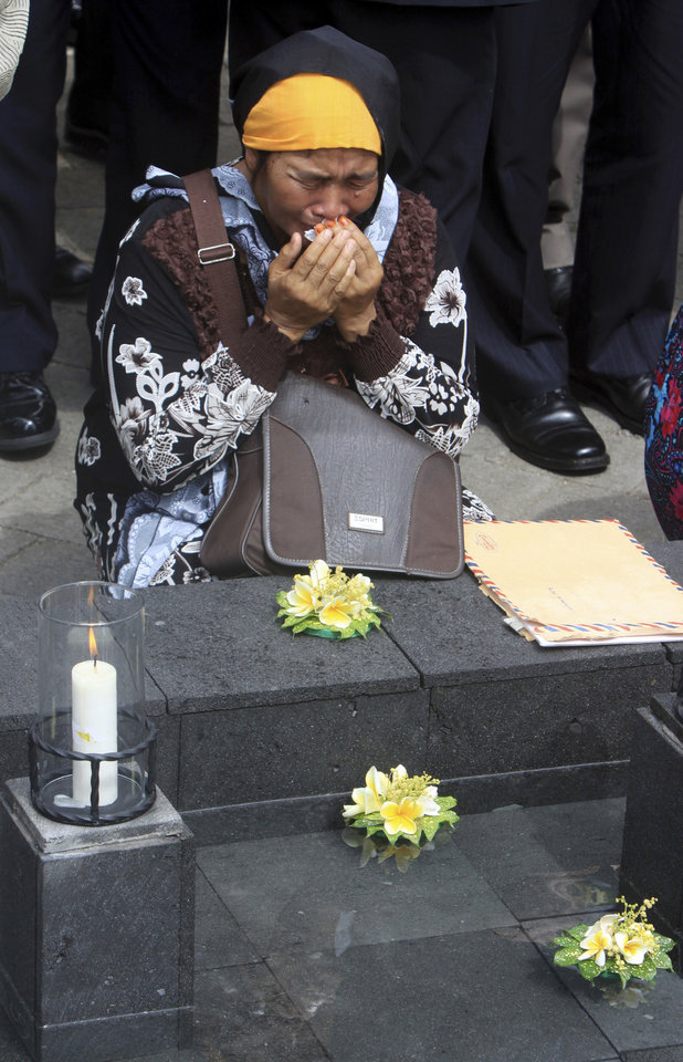 An Indonesian woman grieves for victims of the 2002 Bali bombings at a memorial pond during a memorial service to mark the 10th anniversary of the terrorists attacks in Kuta, in Jimbaran in Bali, Indonesia, Friday, Oct. 12, 2012. A decade after twin bombs killed scores of tourists partying at two beachfront nightclubs on Indonesia's resort island of Bali, survivors and victims' families on Friday braved a fresh terrorism threat to remember those lost to the tragedy. (AP Photo/Firdia Lisnawati)