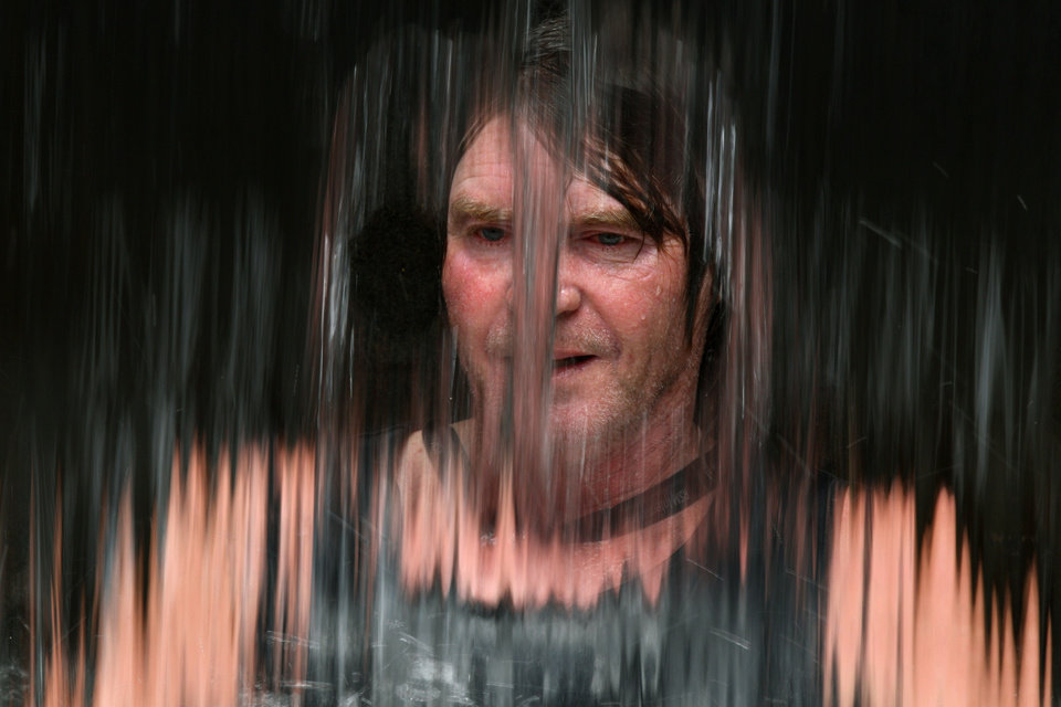 John O\'Reilly takes refuge in the cool water behind a waterfall of a fountain in central Sydney, Australia, Tuesday, Jan. 8, 2013, as the temperature reaches 42 degrees Celsius (107.6. degrees Fahrenheit). Temperatures across much of New South Wales state are expected to reach 45 degrees Celsius (113 degrees Fahrenheit) creating severe wildfire conditions. (AP Photo/Rick Rycroft)