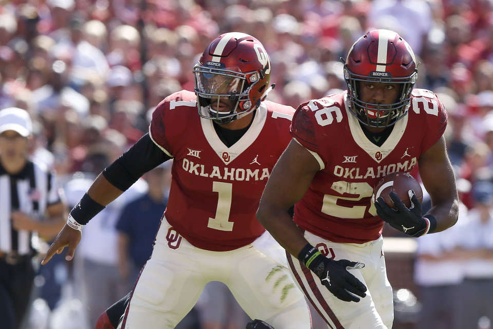 Photo - Oklahoma's Jalen Hurts (1) hands the ball off to Kennedy Brooks (26) during a college football game between the University of Oklahoma Sooners (OU) and the West Virginia Mountaineers at Gaylord Family-Oklahoma Memorial Stadium in Norman, Okla, Saturday, Oct. 19, 2019. Oklahoma won 52-14. [Bryan Terry/The Oklahoman]