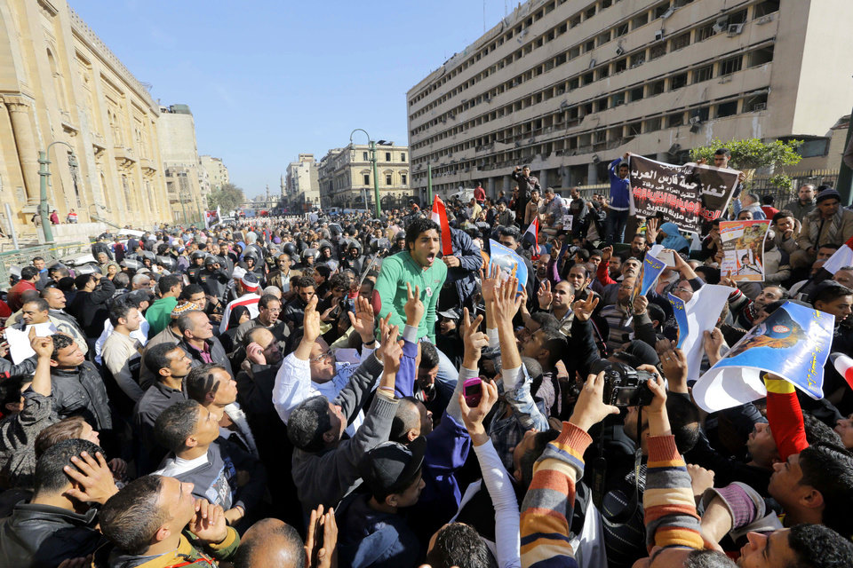 Photo - Egyptians shout anti-terrorism slogans as they demonstrate in front the site of a blast at the Egyptian police headquarters, at right, and the Museum of Islamic Art, at left, in downtown Cairo, Egypt, Friday, Jan. 24, 2014. A car bomb struck the main Egyptian police headquarters Friday in the heart of Cairo, killing several people in a hugely symbolic attack on the eve of the third anniversary of the 2011 uprising that toppled longtime autocratic ruler Hosni Mubarak. (AP Photo/Amr Nabil)