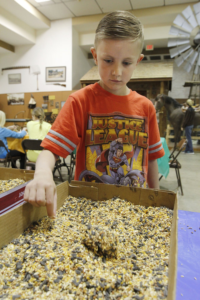 Alex Fowler, 6, packs peanut butter and bird seed into a pine cone to create a bird feeder.