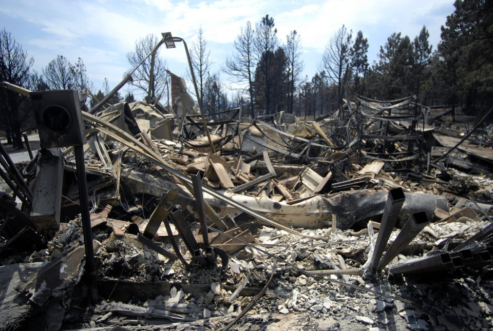Homes are left in ruins after being destroyed by the Waldo Canyon Fire in the Mountain Shadows neighborhood of Colorado Springs, Colo., on Monday, July 2, 2012. So far, the blaze, now 45 percent contained, has damaged or destroyed nearly 350 homes. (AP Photo/Bryan Oller) ORG XMIT: COBO108