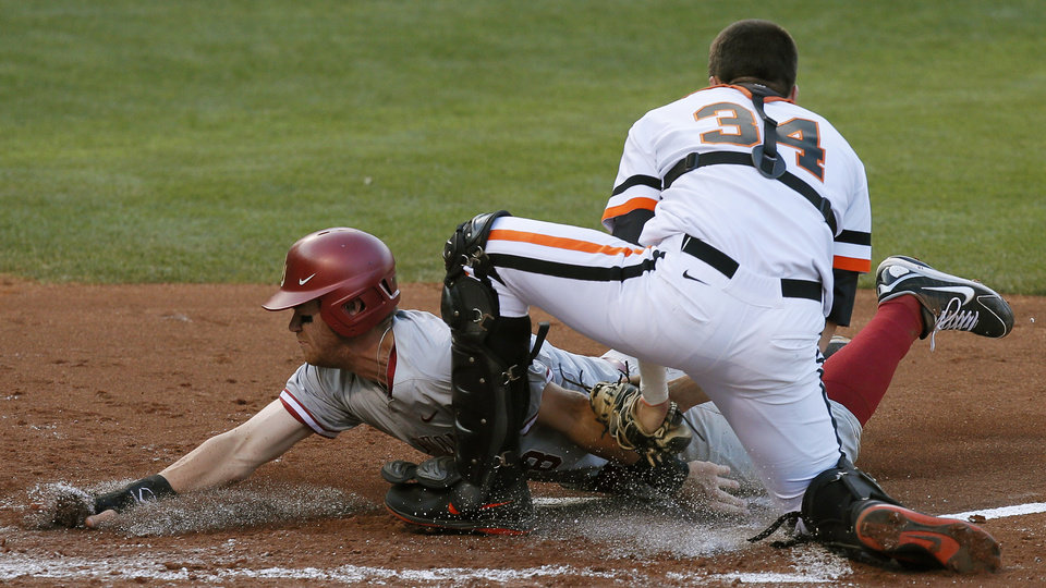 Oklahoma State's  Bryan Case tags out Oklahoma's Mac James at home in the second inning of a college baseball game in Oklahoma City, Thursday, May 15, 2014. (AP Photo/The Oklahoman, Bryan Terry)