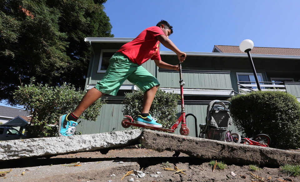 Photo - A youngster rides his scooter over a sidewalk buckled by an earthquake Sunday, Aug. 24, 2014, in Napa, Calif. A large earthquake caused significant damage and left at least three critically injured in California's northern Bay Area early Sunday, igniting fires, sending at least 87 people to a hospital, knocking out power to tens of thousands and sending residents running out of their homes in the darkness. (AP Photo/Rich Pedroncelli)