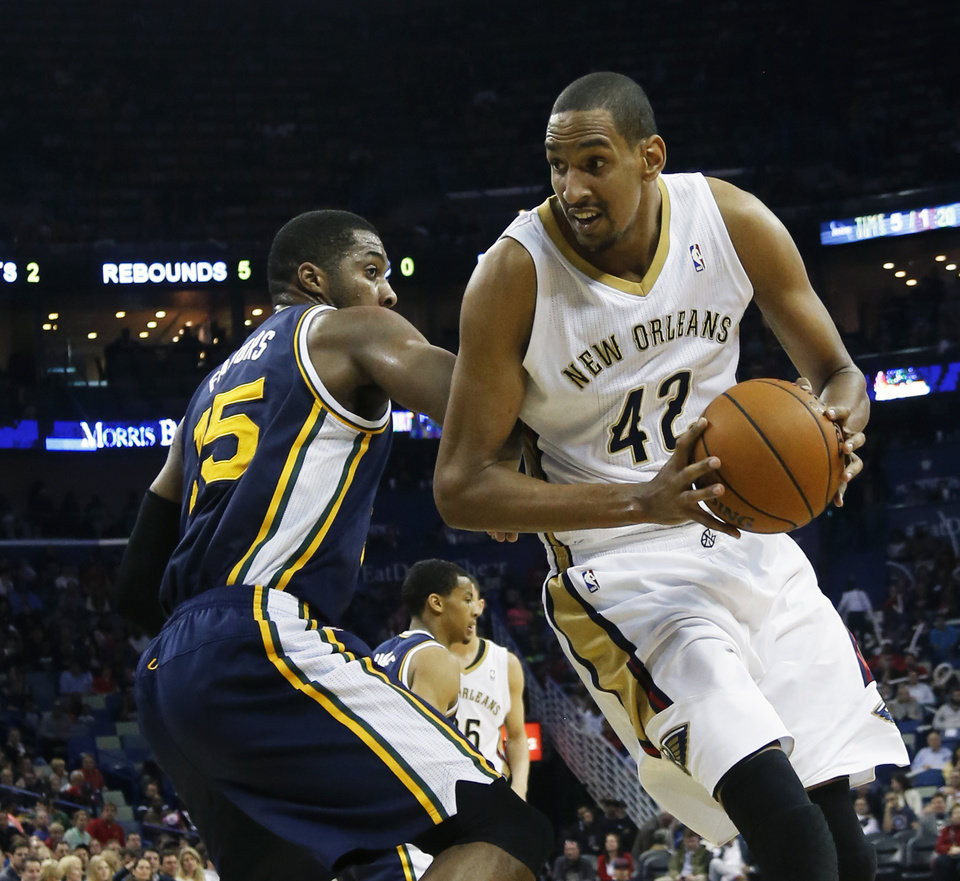 Photo - New Orleans Pelicans center Alexis Ajinca (42) gets by Utah Jazz center Derrick Favors (15) in the first half of an NBA basketball game in New Orleans, Friday, March 28, 2014. (AP Photo/Bill Haber)
