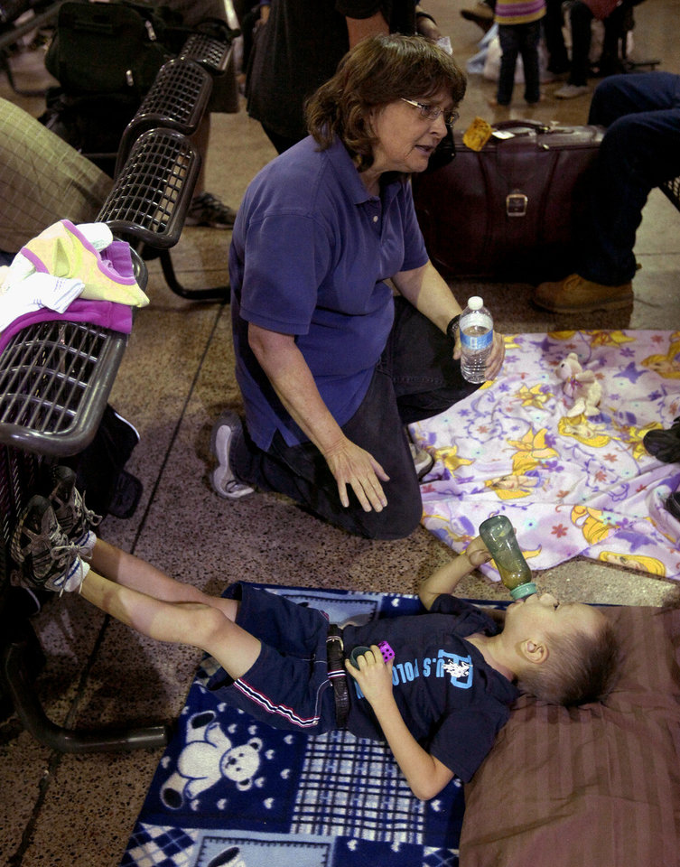 Photo - Volunteer nurse Ronda Kelso, of Phoenix, top, tends to a little boy named Leonel, Thursday, May 29, 2014 at the Greyhound bus terminal in Phoenix. About 400 mostly Central American women and children caught crossing from Mexico into south Texas were flown to Arizona this weekend after border agents there ran out of space and resources.  Officials then dropped hundreds of them off at Phoenix and Tucson Greyhound stations, overwhelming the stations and humanitarian groups who were trying to help. (AP Photo/Rick Scuteri)