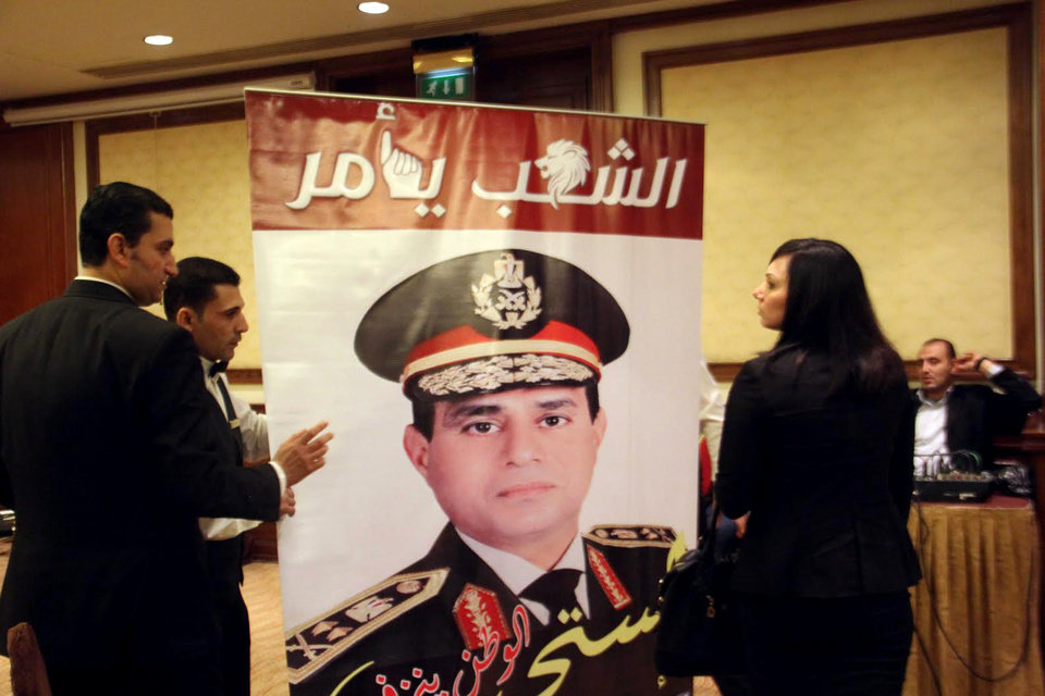Photo - Supporters of Egypt's Defense Minister, Gen. Abdel-Fattah el-Sissi hold a poster bearing his picture with Arabic that reads,