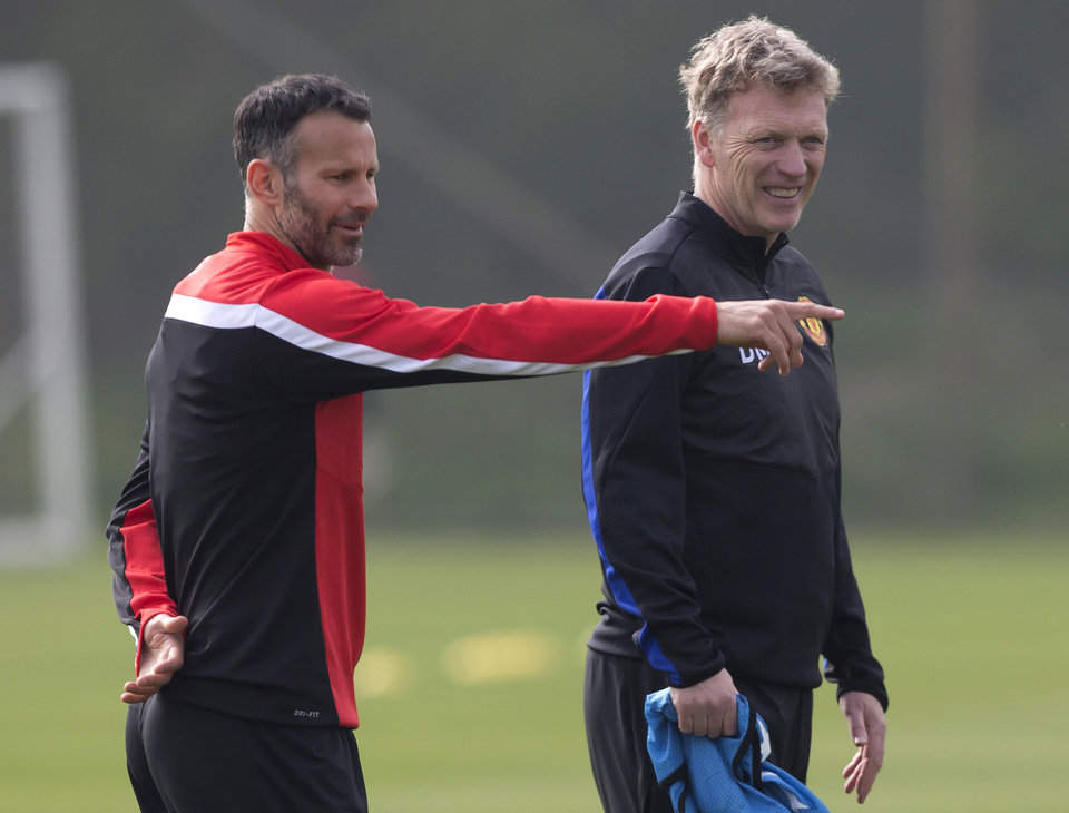Photo - FILE - In this Monday, March 31, 2014 file photo Manchester United's manager David Moyes, right, stands alongside Ryan Giggs as the team trains at Carrington training ground in Manchester. Manchester United says manager David Moyes has left the Premier League club after less than a year in charge, amid heavy speculation he was about to be fired. United released a brief statement in its website Tuesday, saying the club