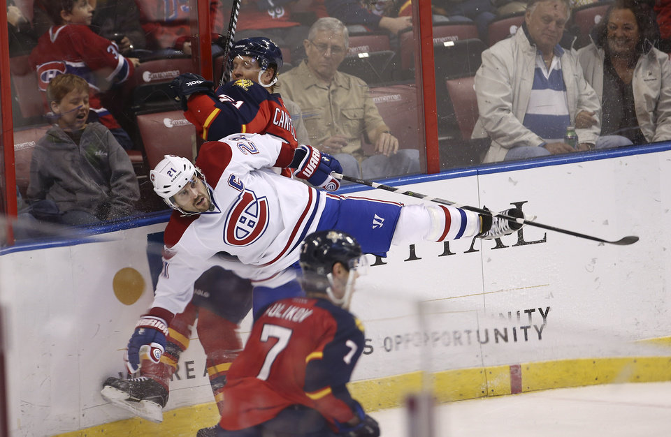 Photo - Montreal Canadiens' Brian Gionta (21) and Florida Panthers' Brian Campbell (51) slam into the baords during the second period of an NHL hockey game in Sunrise, Fla., Saturday, March 29, 2014. (AP Photo/J Pat Carter)