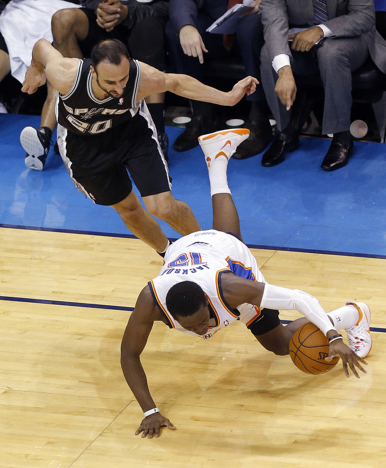 Photo - Oklahoma City's Reggie Jackson (15) falls as San Antonio's Manu Ginobili defends during Game 4 of the Western Conference Finals in the NBA playoffs between the Oklahoma City Thunder and the San Antonio Spurs at Chesapeake Energy Arena in Oklahoma City, Tuesday, May 27, 2014. Photo by Nate Billings, The Oklahoman