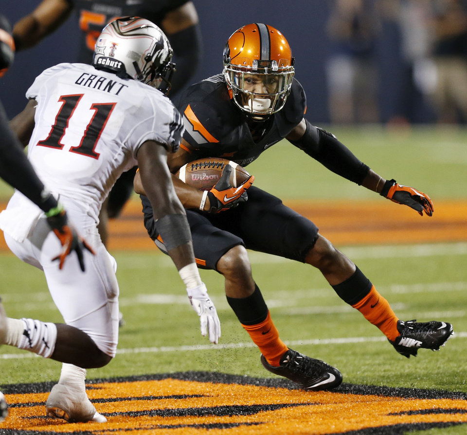 Photo - Oklahoma State's Kevin Peterson (1) tries to get past Texas Tech's Jakeem Grant (11) after intercepting the ball in the second quarter during a college football game between the Oklahoma State Cowboys (OSU) and the Texas Tech Red Raiders at Boone Pickens Stadium in Stillwater, Okla., Thursday, Sept. 25, 2014. Photo by Nate Billings, The Oklahoman