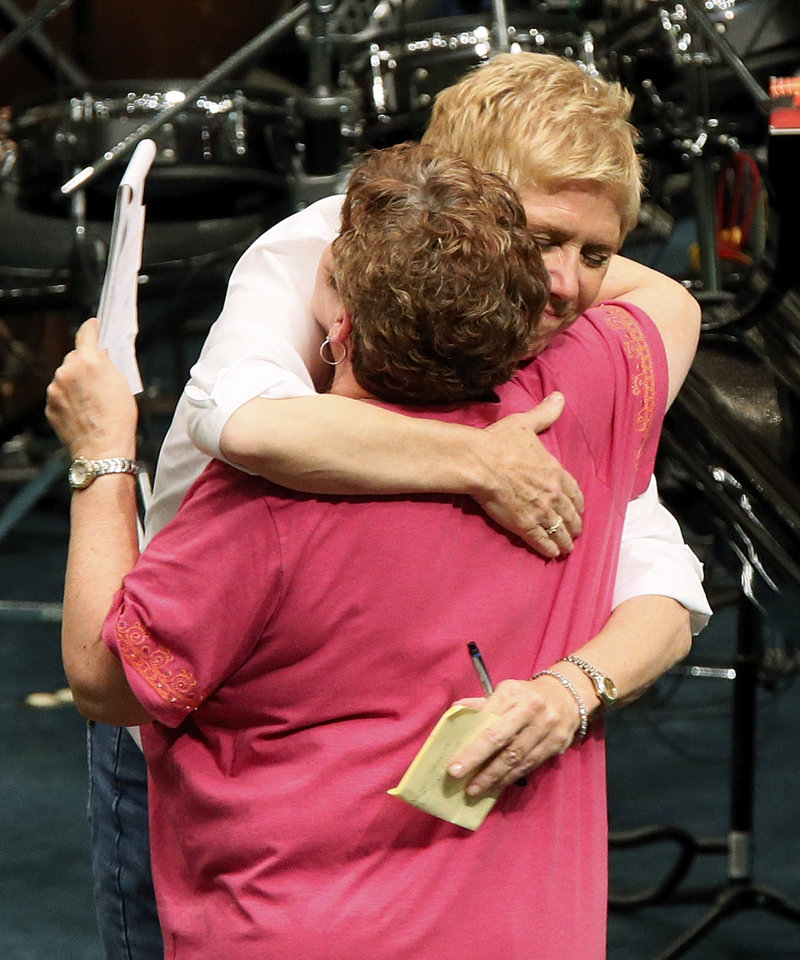 Photo - State superintendent Janet Barresi, back, hugs Moore Public Schools superintendent Susan Pierce during a district-wide meeting of Moore Public Schools employees at Southern Hills Baptist Church, 8601 Pennsylvania Ave., in Oklahoma City, Wednesday, May 22, 2013, after a tornado struck south Oklahoma City and Moore, Okla., on Monday. Photo by Nate Billings, The Oklahoman
