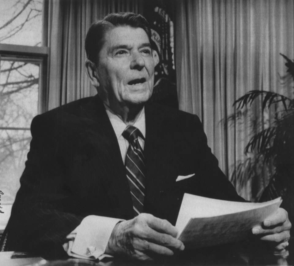 Photo - President Ronald Reagan posed for photographers in the White House Oval Office after he addressed NASA employees via a satellite television hookup. The president, saying Americans should learn the