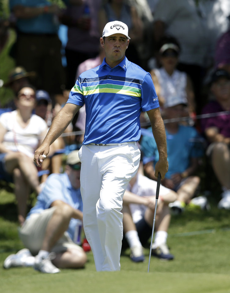 Photo - Gary Woodland reacts as he's unable to sink a putt for birdie on the second green during the final round of the Byron Nelson Championship golf tournament, Sunday, May 18, 2014, in Irving, Texas. (AP Photo/Tony Gutierrez)