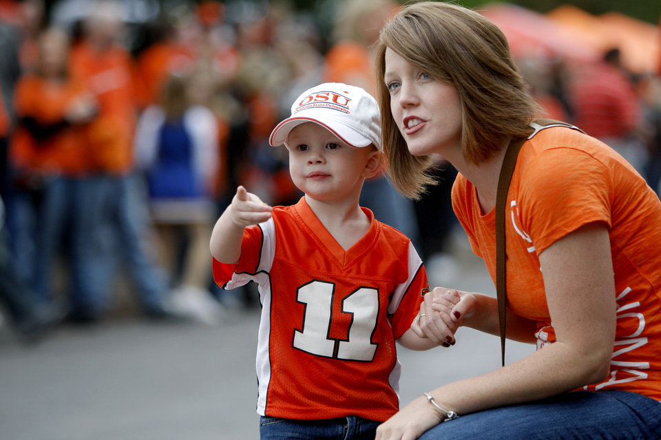 Photo - Lindsey Barber of Sapulpa, Okla., waits with her cousin Max Gipson, 2, of Edmond, Okla., for the Spirit Walk before the college football game between the Oklahoma State Cowboys (OSU) and the Nebraska Huskers (NU) at Boone Pickens Stadium in Stillwater, Okla., Saturday, Oct. 23, 2010. Photo by Bryan Terry, The Oklahoman