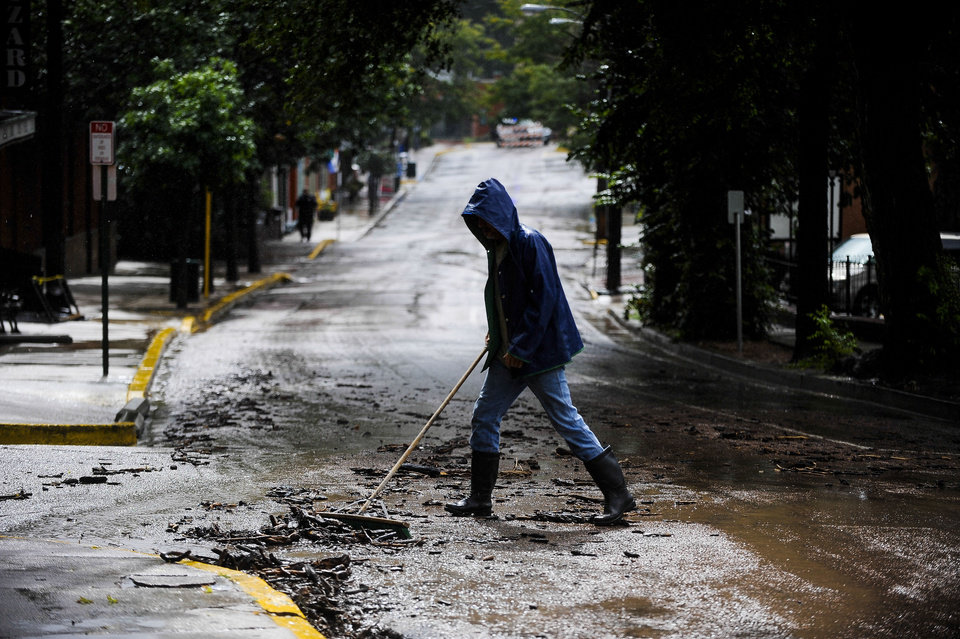 Photo - A man begins cleaning up Canon Avenue in Manitou Springs, Colo. after a flash flood burst through a manhole and sent water rushing down the streets Thursday, Sept. 12, 2013. (AP Photo/The Gazette, Michael Ciaglo) MAGS OUT