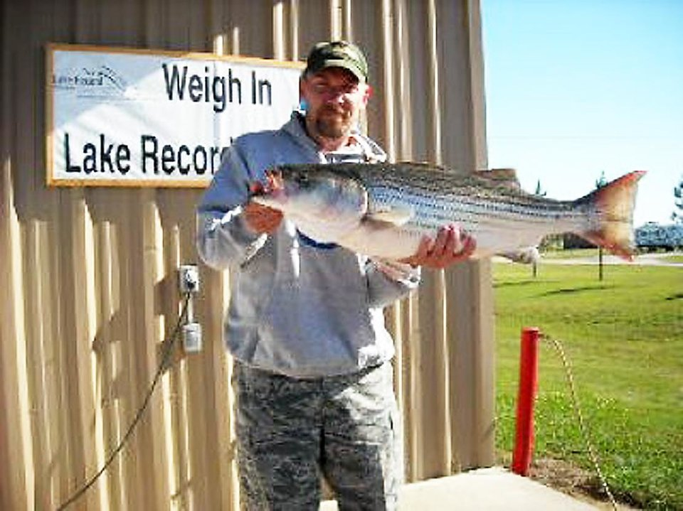 Steve DeSomer of Harrah holds a 20.4-striped bass that he caught from Lake Texoma which is the new lake record. <strong>Photo provided</strong>
