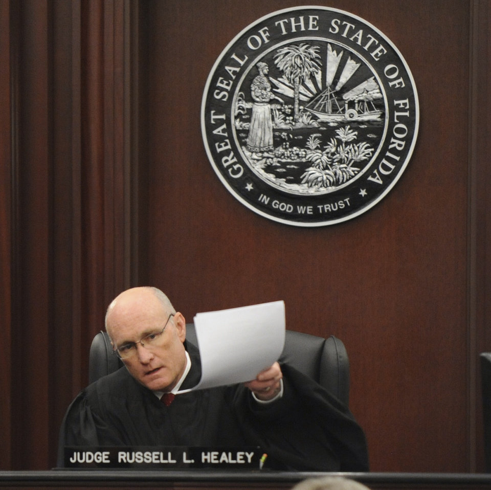 Photo - Judge Russell Healey holds up documents as he announces that the jury is deadlocked on charge one and have verdicts in the other four charges while deliberating, Saturday Feb. 15, 2014 in the trial of Michael Dunn for the shooting death of Jordan Davis in November 2012. The judge has asked jurors to continue deliberating on the fate of the Florida man charged with fatally shooting the teen after an argument over loud music because the panel expressed difficulty. (AP Photo/The Florida Times-Union, Bob Mack, Pool)