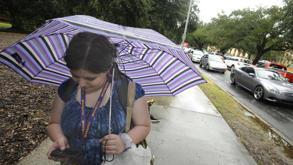 Photo -   LSU student Michelle Bourgoyne, 19, texts on her cellphone while waiting for a bus as traffic on campus is gridlocked after a bomb threat forced evacuation Monday morning, Sept. 17, 2012 in Baton Rouge, La. Bourgoyne, an English major, said she had two classes before the evacuation order was made. (AP Photo/The Advocate, Patrick Dennis) MAGS OUT; INTERNET OUT; ONLINE OUT; NO SALES; TV OUT; FOREIGN OUT; LOUISIANA BUSINESS INC OUT(GREATER BATON ROUGE BUSINESS REPORT OUT, 225 OUT, 10/12 OUT, IN REGISTER OUT, LBI CUSTOM PUBLICATIONS OUT)