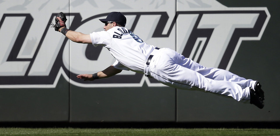 Photo - Seattle Mariners left fielder Willie Bloomquist goes airborne after snagging a line drive by Oakland Athletics's Craig Gentry in the ninth inning of a baseball game Sunday, April 13, 2014, in Seattle. Oakland won 3-0. (AP Photo/Elaine Thompson)