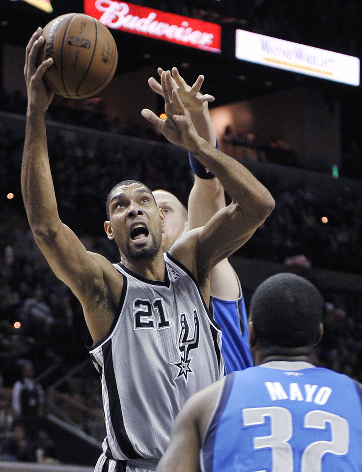 San Antonio Spurs' Tim Duncan (21) shoots between Dallas Mavericks' O.J. Mayo (32) and Chris Kaman during the first half of an NBA basketball game, Sunday, Dec. 23, 2012, in San Antonio. (AP Photo/Darren Abate)
