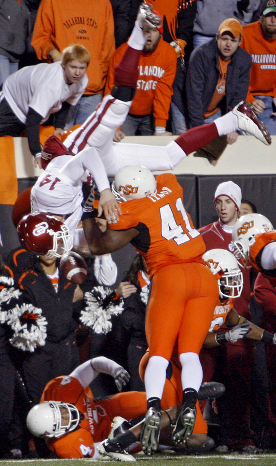 BEDLAM / FLIP: Oklahoma quarterback Sam Bradford (14) is flipped upside down as he leaps over Oklahoma State's Orie Lemon (41) during the second half of the college football game between the University of Oklahoma Sooners (OU) and Oklahoma State University Cowboys (OSU) at Boone Pickens Stadium on Saturday, Nov. 29, 2008, in Stillwater, Okla. STAFF PHOTO BY CHRIS  LANDSBERGER    ORG XMIT: KOD