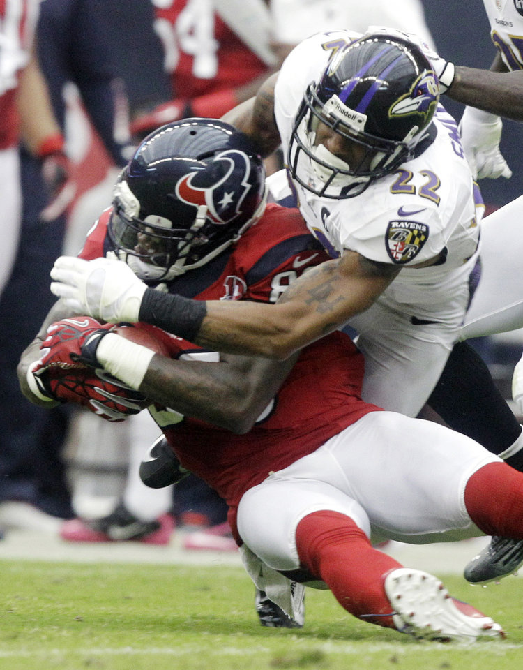 Photo -   Baltimore Ravens defensive back Jimmy Smith (22) tackles Houston Texans wide receiver Andre Johnson (80) during the second quarter of an NFL football game on Sunday, Oct. 21, 2012, in Houston. (AP Photo/Patric Schneider)