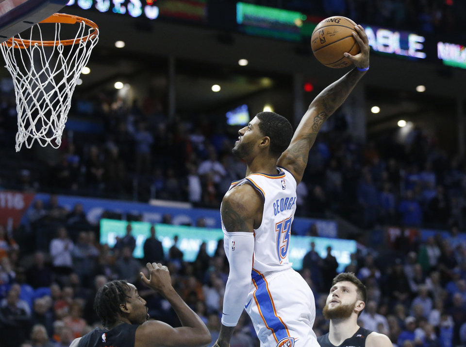 Photo - Oklahoma City Thunder forward Paul George (13) goes up for a dunk between Portland Trail Blazers forward Al-Farouq Aminu, left, and center Jusuf Nurkic, right, in the first half of an NBA basketball game in Oklahoma City, Monday, Feb. 11, 2019. (AP Photo/Sue Ogrocki)