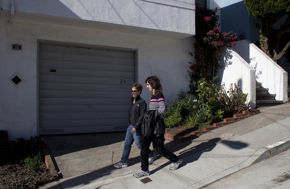 Photo -   In this photo taken Monday, Nov. 12, 2012, Amy Cunninghis, left, and Karen Golinski, right, walk down a street near their home in San Francisco. All Golinski wanted was to enroll her spouse in her employer-sponsored health plan. Four years later, her request still is being debated. Because Golinski is married to another woman and she works for the federal government, her personal personnel problem has morphed into a multi-pronged legal attack by gay rights activists to overturn the 1996 law that defines marriage as the union of a man and a woman. (AP Photo/Eric Risberg)