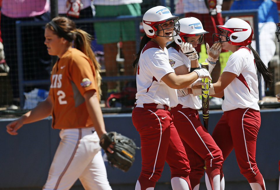 Photo - From left, Texas pitcher Kim Bruins (2) walks away from OU's Lauren Chamberlain (44), Brianna Turang (2) and Destinee Martinez (00) as they celebrate scores by Turang, Martinez and and Callie Parsons (12), not pictured, in the third inning during an NCAA softball game in the Women's College World Series between Oklahoma and Texas at ASA Hall of Fame Stadium in Oklahoma City, Saturday, June 1, 2013. Oklahoma won 10-2 in five innings. Photo by Nate Billings, The Oklahoman