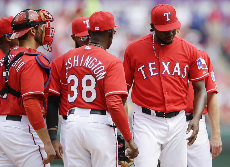 Photo - As J.P. Arencibia (7) looks on, Texas Rangers manager Ron Washington (38) takes relief pitcher Pedro Figueroa, right, out of the game during the sixth inning of an opening day baseball game against the Philadelphia Phillies at Globe Life Park, Monday, March 31, 2014, in Arlington, Texas.  (AP Photo/Tony Gutierrez)