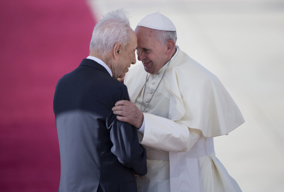 Photo - Pope Francis, right, talks with Israeli President Shimon Peres, during an official arrival ceremony at Ben Gurion airport near Tel Aviv, Israel, Sunday, May 25, 2014.  Pope Francis took a dramatic plunge Sunday into Mideast politics while on his Holy Land pilgrimage, receiving an acceptance from the Israeli and Palestinian presidents to visit him at the Vatican next month to discuss embattled peace efforts. The summit was an important moral victory for the pope, who is named after the peace-loving Francis of Assisi. Israeli-Palestinian peace talks broke down in late April, and there have been no public high-level meetings for a year. (AP Photo/Oded Balilty)