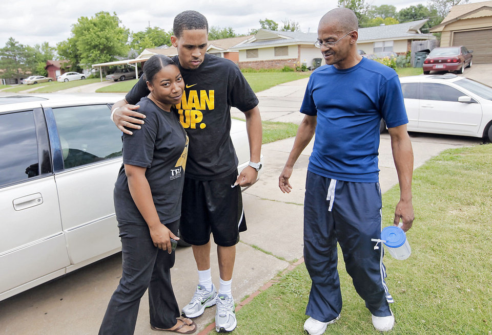 Photo - Bricktown shooting victim Norman Richards II gets a hug from his cousin, Nicolette Anderson, on Friday in the front driveway of his Del City home as his father, Norman Richards Sr., watches.  Photo by Chris Landsberger, The Oklahoman