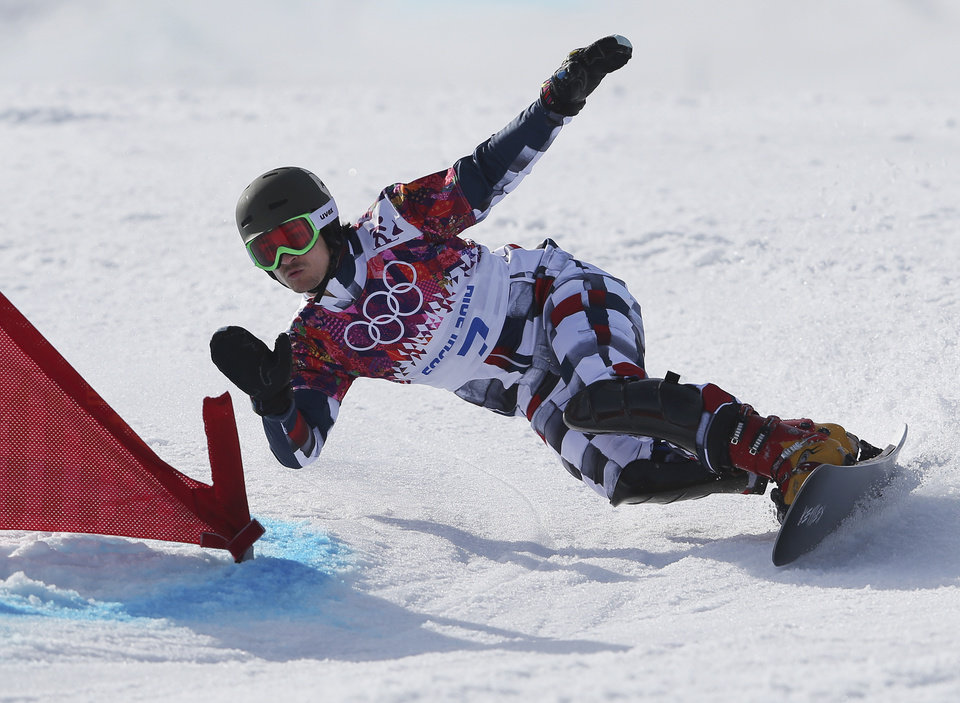 Photo - Russia's Vic Wild competes on the way to winning the men's snowboard parallel giant slalom semifinal at the Rosa Khutor Extreme Park, at the 2014 Winter Olympics, Wednesday, Feb. 19, 2014, in Krasnaya Polyana, Russia.  (AP Photo/Sergei Grits)