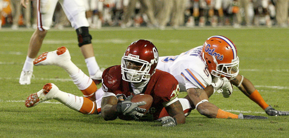 Photo - OU's Chris Brown comes up short on a fourth down as Florida's Joe Haden brings him down during the first half of the BCS National Championship college football game between the University of Oklahoma Sooners (OU) and the University of Florida Gators (UF) on Thursday, Jan. 8, 2009, at Dolphin Stadium in Miami Gardens, Fla. 