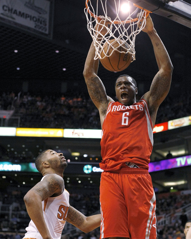 Photo - Houston Rockets power forward Terrence Jones (6), right, dunks on Phoenix Suns power forward Marcus Morris (15) in the first quarter during an NBA basketball game, Sunday, Feb. 23, 2014, in Phoenix. (AP Photo/Rick Scuteri)