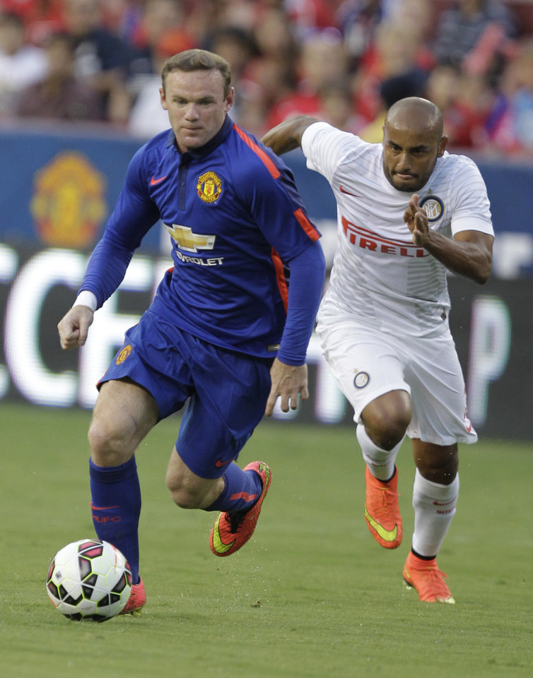 Photo - Manchester United's Wayne Rooney, front moves the ball as Inter Milan's Jonathan, right, defends during the first half of a soccer game at  the 2014 Guinness International Champions Cup, Tuesday, July 29, 2014, in Landover, Md.  Manchester United won 5-3 in a penalty shootout. (AP Photo/Luis M. Alvarez)