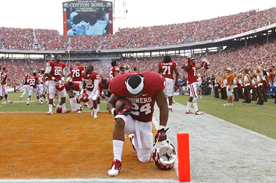 Photo - OU's Brennan Clay (24) kneels in prayer during the Red River Rivalry college football game between the University of Oklahoma (OU) and the University of Texas (UT) at the Cotton Bowl in Dallas, Saturday, Oct. 13, 2012. Photo by Chris Landsberger, The Oklahoman