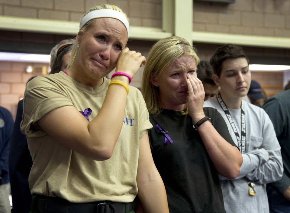 Photo - Firefighters Kayla Garst, left, and Darce Knight react during a memorial service, Monday, July 1, 2013 in Prescott, Ariz. The service was held for the 19 Granite Mountain Hotshot Crew firefighters who were killed Sunday, when an out-of-control blaze overtook the elite group. (AP Photo/Julie Jacobson)