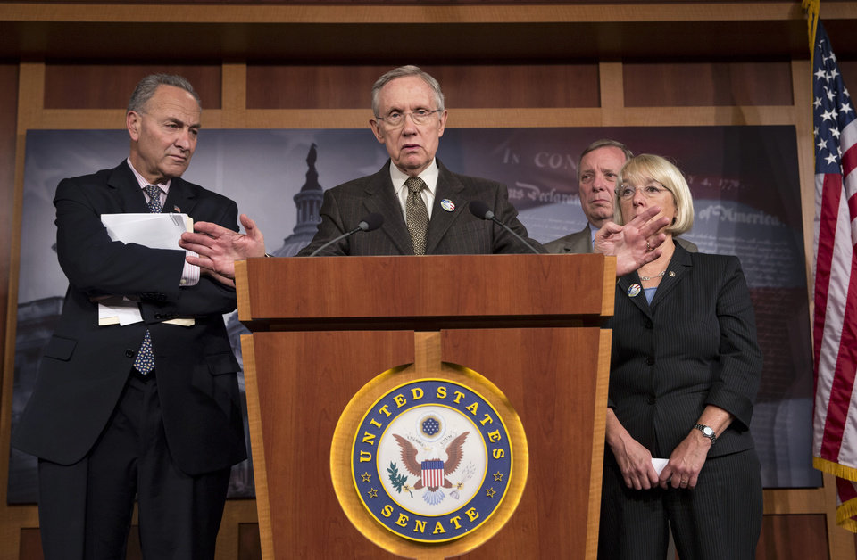 Photo - Senate Majority Leader Harry Reid of Nev., center, accompanied by Democratic leaders, gestures during a news conference on Capitol Hill in Washington, Friday, Oct. 4, 2013, where he told reporters that House Speaker  John Boehner of Ohio, and House Republicans are the obstacle to ending the government shutdown crisis. From left are, Sen. Charles Schumer, D-N.Y., Reid, Senate Majority Whip Richard Durbin of Ill., and Senate Budget Committee Chair Sen. Patty Murray, D-Wash. (AP Photo/J. Scott Applewhite)