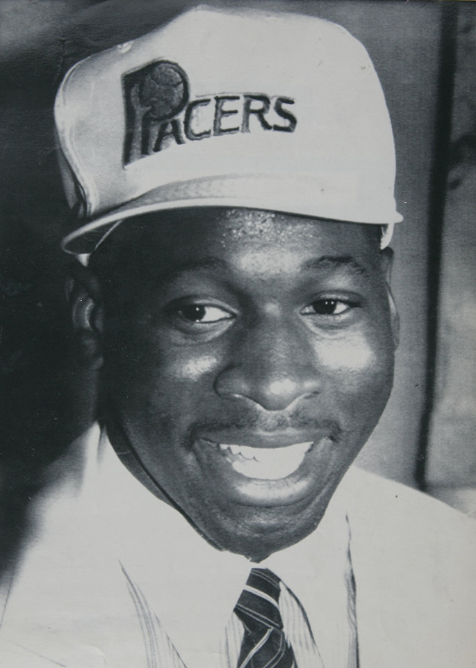 Photo - Former OU basketball player Wayman Tisdale. New York, June 18 -- TISDALE TO PACERS --    NBA BASKETBALL: Wayman Tisdale, 2nd pick in the first round of the NBA draft, tries on his new Indiana Pacers cap on Tuesday in New York. stf/Marty Lederhandler - 1985. ORG XMIT: KOD