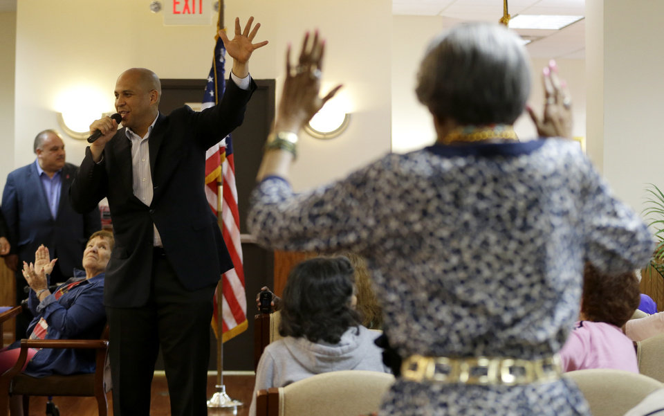 Photo - Harriet Drake, right, gets off her seat to respond while Newark Mayor Cory Booker addresses supporters at a senior center, Tuesday, Oct. 15, 2013, in Newark, N.J. Booker will be going up against his Republican opponent Steve Lonegan Wednesday, Oct. 16, during a special election to fill New Jersey's vacant seat in the U.S. Senate. (AP Photo/Julio Cortez)