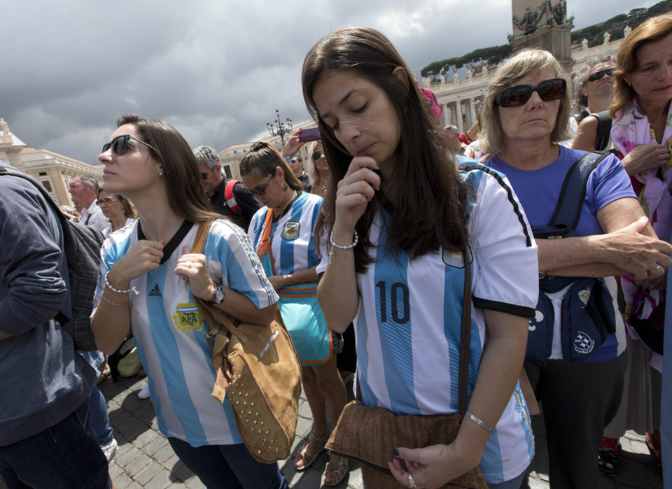 Photo - Faithful wearing Argentina soccer team jerseys pray as Pope Francis delivers the Angelus prayer in St. Peter square at the Vatican, Sunday, July 13, 2014. The Argentine-born, football-loving pontiff pledged neutrality, promising not to pray for any team. However, Francis did tweet on the eve of the final: